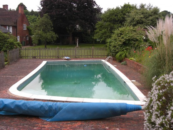 Original condition of pool irregular shape with old solar cover